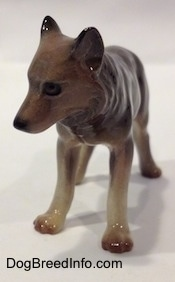 A figurine of a brown with tan Wolf. The figurine has a detailed face.