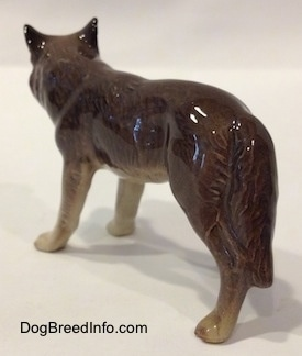 The back left side of a brown with tan figurine of a Wolf. The figurine has long tail that hang next to its leg.
