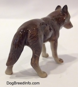 The back right side of a brown with tan Wolf figurine. The figurine has its ears in the air.