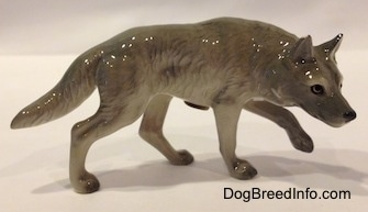 The right side of a stalking gray Wolf figurine. The figurine is glossy.