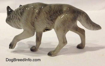 The left side of a stalking figurine of a gray Wolf. The figurine has a long tail.