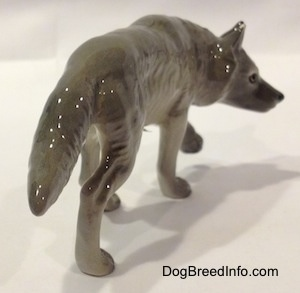 The back right side of a figurine of a stalking gray Wolf.