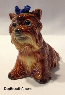 The front left side of a brown with tan Yorkshire Terrier sitting figurine. The figurine has a blue bow in its hair.