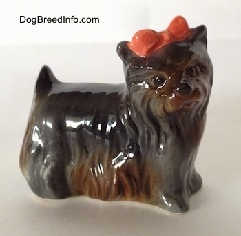 The right side of a gray with brown figurine of a Yorkshire Terrier that has a red bow in its hair.