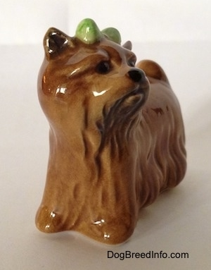 The front left side of a brown figurine of a Yorkshire Terrier figurine. The figurine has a black nose and small black circles for eyes.