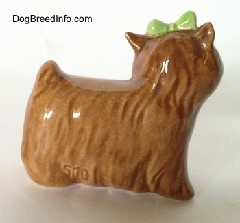 The right side of a brown Yorkshire Terrier figurine with a green bow in its hair. Its ears are small and sticking in the air.