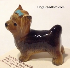The left side of a black with brown Yorkshire Terrier figurine with a bluw bow in its hair. The figurine is glossy.