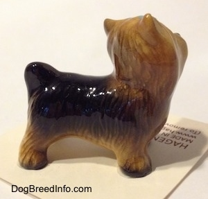The right side of a black with brown Yorkshire Terrier figurine. The figurine has fine hair brushings along its body.