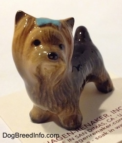 The front right side of a figurine of a black with brown Yorkshire Terrier with a blue bow in its hair. The figurine has black circles for eyes.