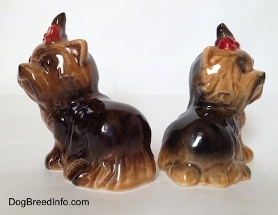 The back side of two black with brown figurines of sitting Yorkshire Terriers. The figurines have short ears.
