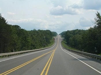 A long highway with a yellow stripe down the center and trees on each side.